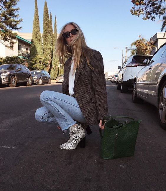 a white tee, blue raw hem jeans, a tweed jacket, snake print boots and a dark green bag