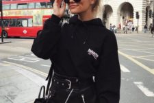 14 an oversized black hoodie, a black mini skirt with a belt and a black bag for a bold and edgy look