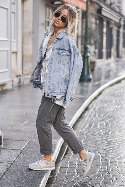 cuffed grey pants, a neutral shirt, a bleached denim jacket and grey trainers for a sport chic look