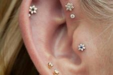 14 lap, daith and tragus piercings with beautiful floral and pearl studs look very girlish