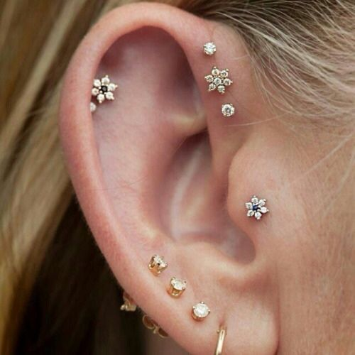 lap, daith and tragus piercings with beautiful floral and pearl studs look very girlish