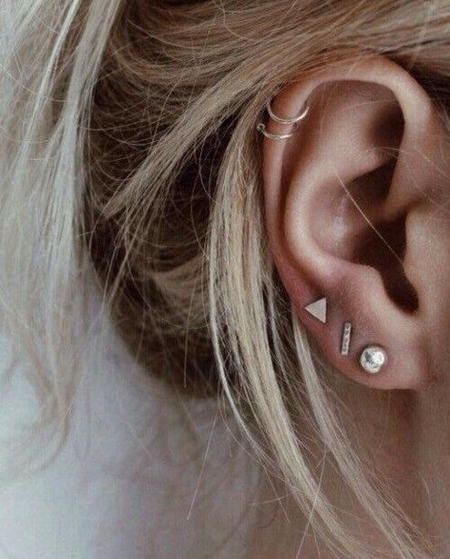 stylish boho ear accessorizing with several ear studs and two hoops iin the helix looks very relaxed