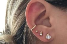 14multiple ear piercings with gold and rhinestone studs and a gold hoop in the lower part of the conch