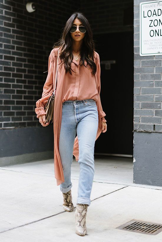 a coral shirt and a duster, blue jeans, snake print boots and a small neutral bag