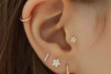 15 lap, helix and tragus piercings with gold hoops and floral studs for a chic and shiny look