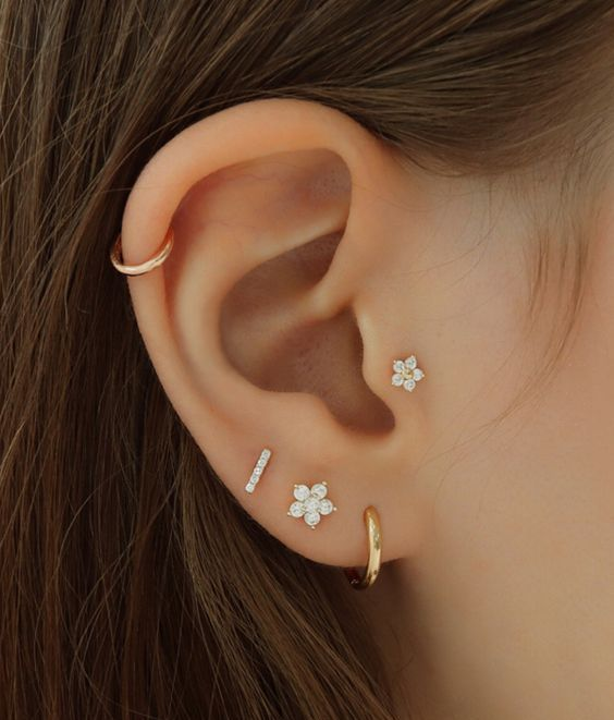 lap, helix and tragus piercings with gold hoops and floral studs for a chic and shiny look