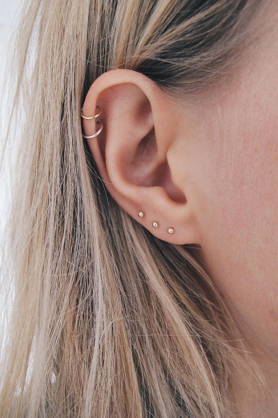 three earrings in the lap and a double piercing in the helix for a bold and cool look