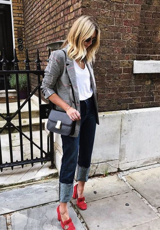 a business casual look with a white top, navy jeans, a plaid blazer, a black bag and red heeled loafers
