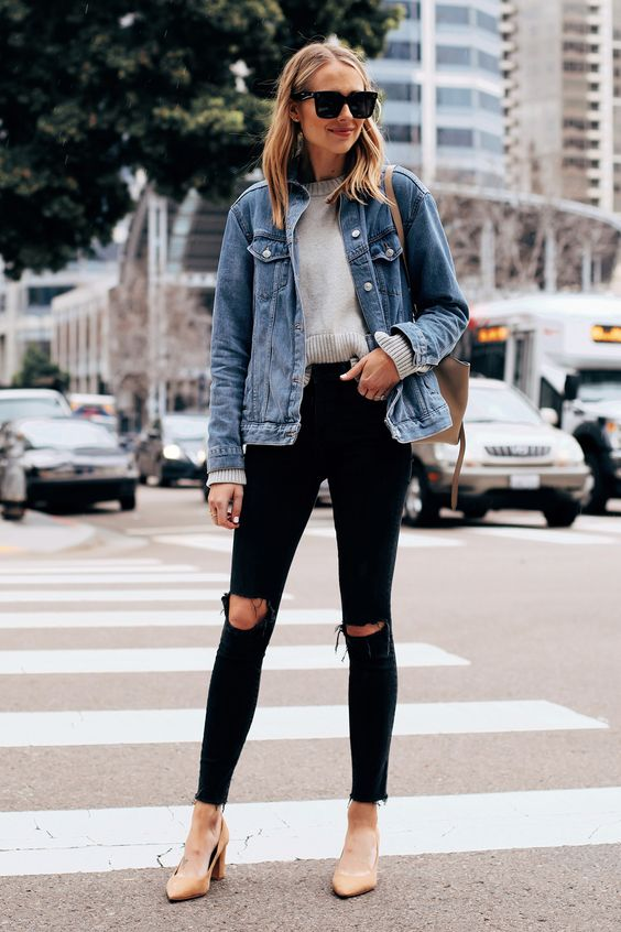 nude heels, a grey cropped sweater, black ripped jeans, a blue denim jacket and a neutral bag