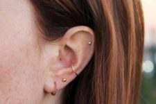 16 simple and stylish ear piercings with gold studs and gold and rhinestone hoops in the daith and conch