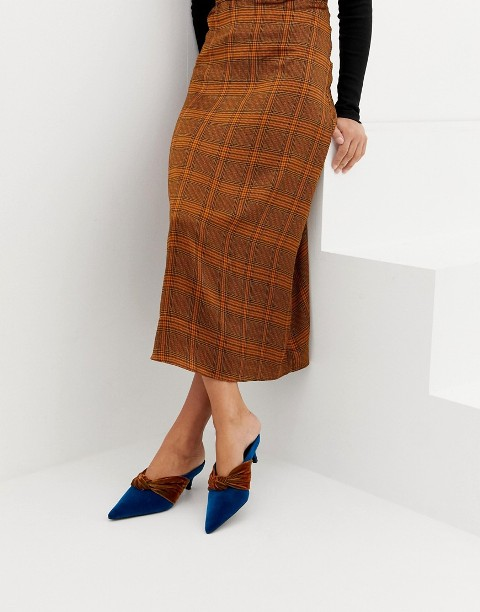 With black shirt and checked midi skirt