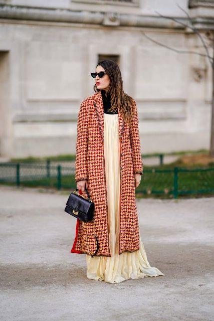 With black turtleneck, beige maxi dress and black bag