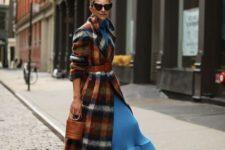 With blue dress, high heels, orange tights and mini bag