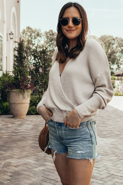 With denim shorts and rounded bag