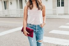 With distressed jeans, velvet clutch and top