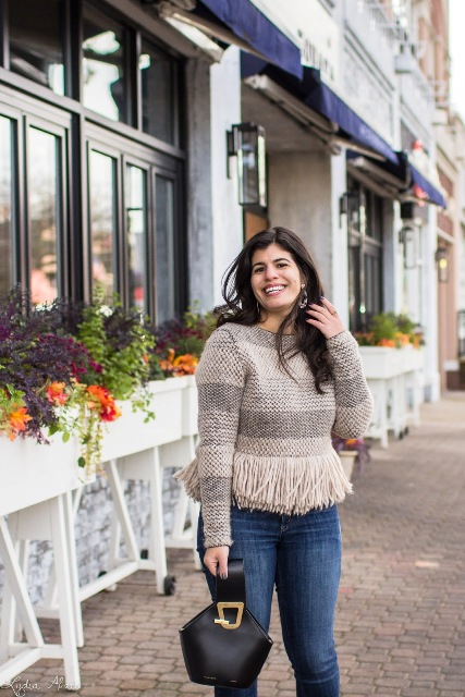 a striped fringe sweater outfit with jeans and black leather small bag