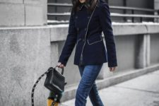 With navy blue jacket, skinny jeans and black small bag