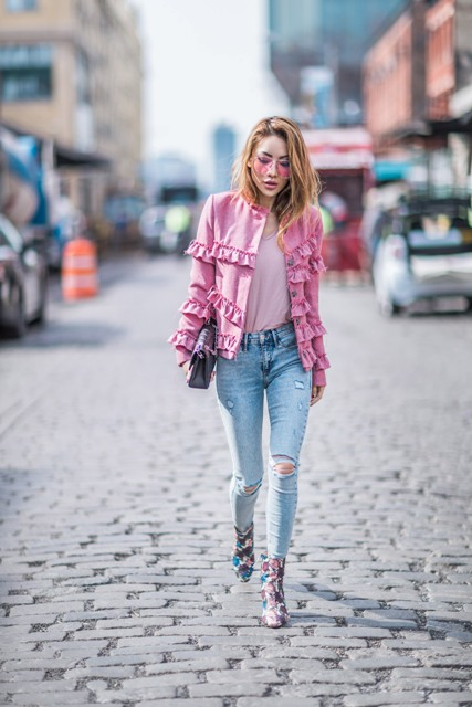 With pale pink t-shirt, ruffled jacket, distressed jeans and clutch