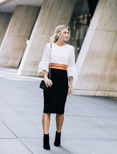 With white blouse, black knee-length skirt, chain strap bag and ankle boots