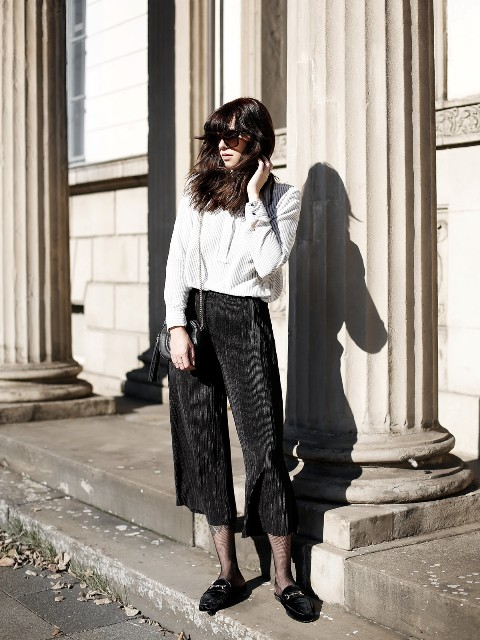 With white loose shirt, chain strap bag and black culottes