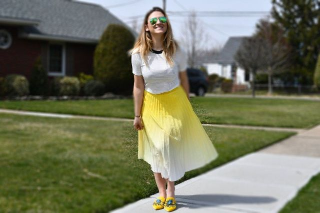 With white t-shirt and yellow embellished flat shoes