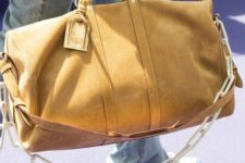 a bold mustard suede travel bag with a decorative chain will add a touch of color and a modern feel to your look