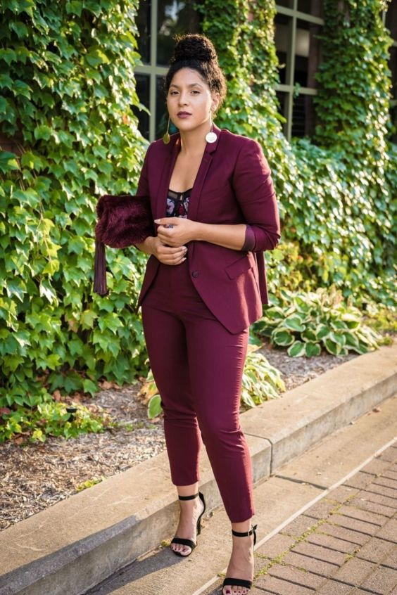 a burgundy pantsuit, a florla bodice, blakc shoes and a burgundy velvet bag can be easily transitioned to a party look