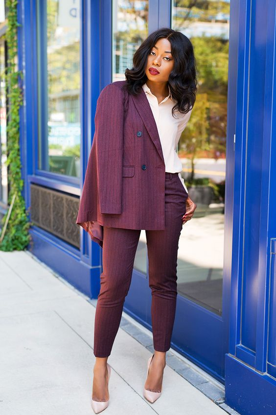 a burgundy striped suit with fitting cropped pants, a blush shirt and blush pumps for a wow effect