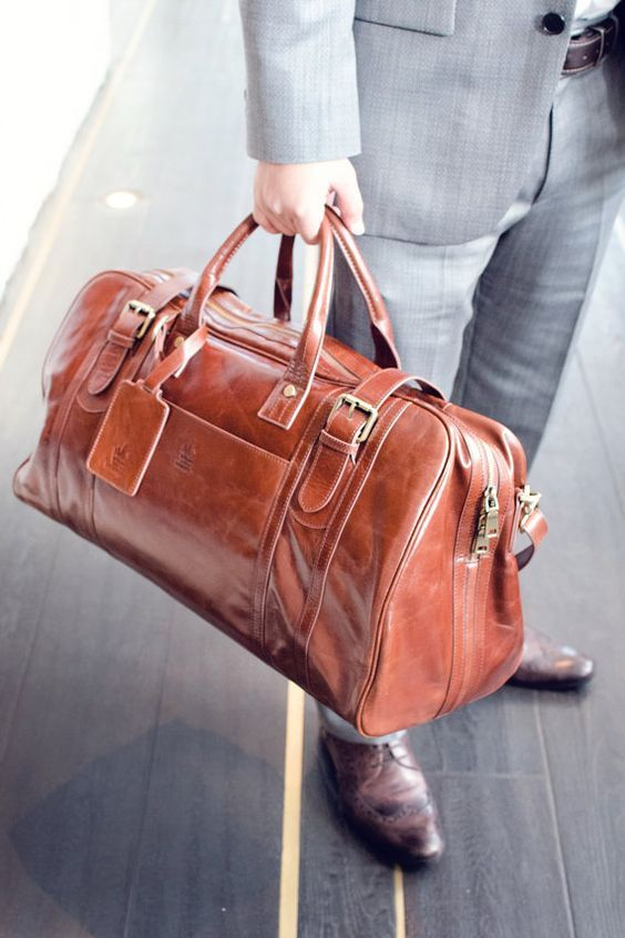 a chic vintage-inspired cognac-colored leather travel bag will add a touch of color and vintage chic to your look