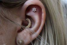 a gold and a floral stud and a matching bright gold hoop earring in the daith will make your ear pop