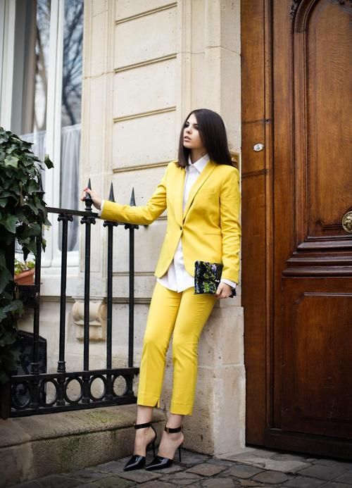 a lemon yellow pantsuit, a white shirt, black pointed toe heels and a floral clutch for a summer or spring feel