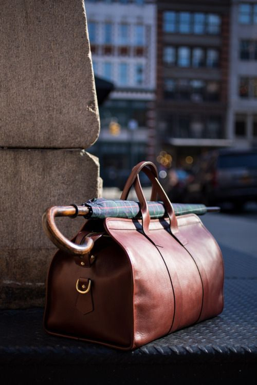 a minimalist and chic brown leather travel bag with longer handles to place your umbrella there