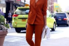 a rust-colored pantsuit, white sneakers and a silver bag for a super modern and bold outfit