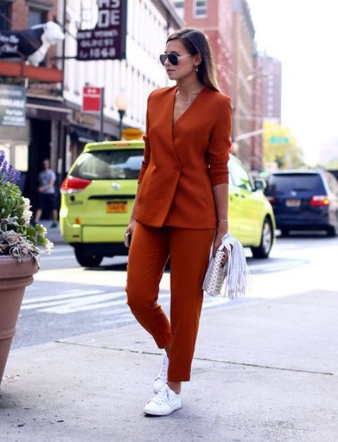 a rust colored pantsuit, white sneakers and a silver bag for a super modern and bold outfit
