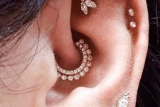all shiny and bright ear accessorizing with studs and hoops plus a shiny rhinestone hoop in the daith