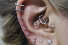 an ear all done with piercings, shiny studs and hoops along the whole helix and a rhinestone hoop in the daith