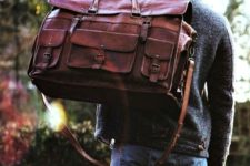 an oversized burgundy travel bag with lots of decorative pockets and belts