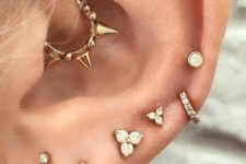 gold and shiny studs and hoops in the ear and a spiky gold hoop in the daith for a bold statement