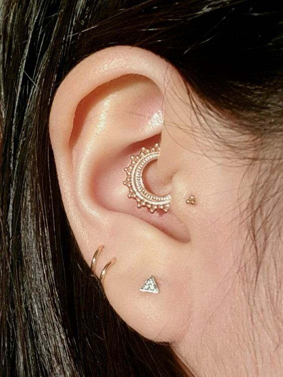 hoops and a triangle stud in the lobe, a stud in the tragus and a bright boho hoop in the daith