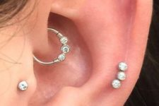shiny ear accessorizing with tiny studs and a studded hoop earring in the daith will highlight your style