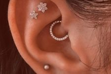 shiny ear accessorizing with usual and floral studs and a shiny rhinestone hoop in the daith