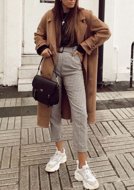 a black long sleeve top, printed pants, a camel coat and grey trainers plus a black bag