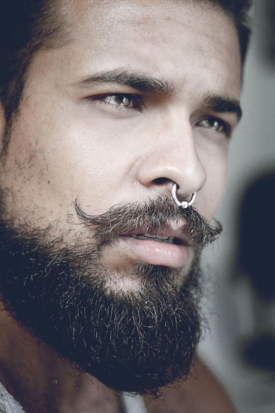 a nose septum piercing with a hoop plus a super edgy beard and moustache for an edgy touch