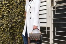 03 a black turtleneck, a white trench, blue cuffed jeans, black trainers and a printed black bag