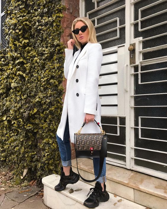 a black turtleneck, a white trench, blue cuffed jeans, black trainers and a printed black bag