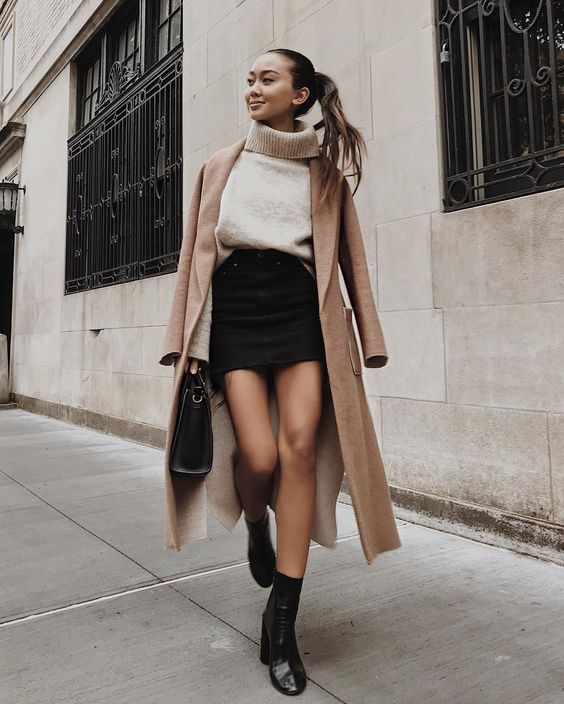 a creamy turtleneck sweater, a black denim mini, black booties, a camel coat and a black bag