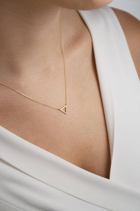 a gold frame triangle necklace on a very thin chain is a very delicate accessory to try