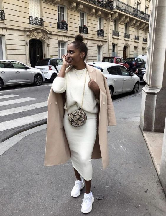 a minimalist fall or winter outfit with a white sweater, a midi pencil skirt, white trainers, a camel coat and a snake print bag