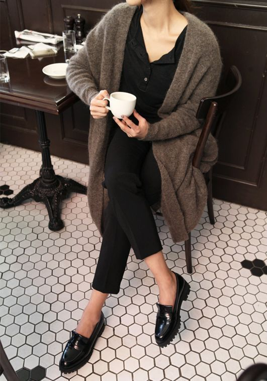 a black shirt, cropped pants, a cozy long brown cardigan and black loafers for a comfy outfit