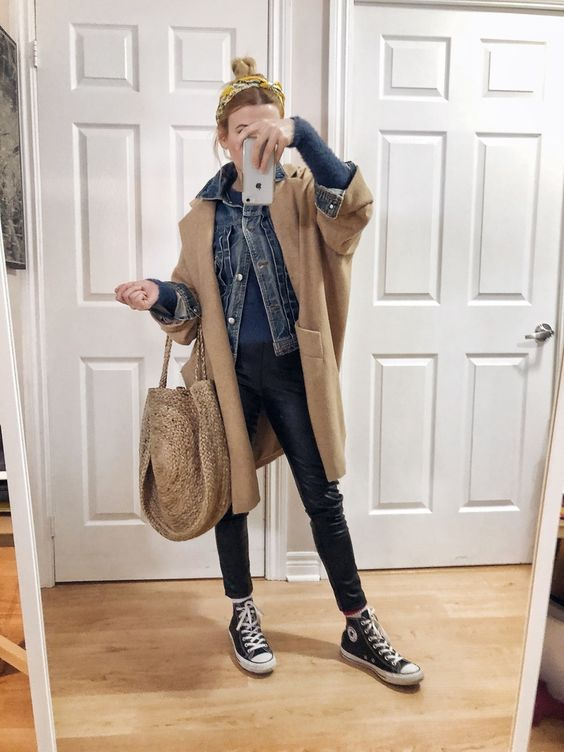 a casual look with black leather pants, a blue sweater, a blue denim jacket, a camel coat, a wicker bag and sneakers